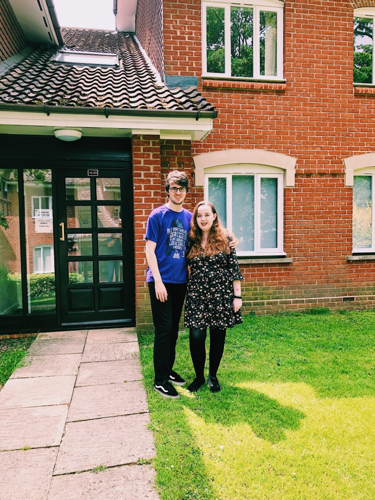Image ID: Charlotte and Erin stood in-front of their flat. Erin is wearing a purple t-shirt and black jeans. Char is wearing a floral dress with black tights. Erin has his arms around Char and both are smiling.
