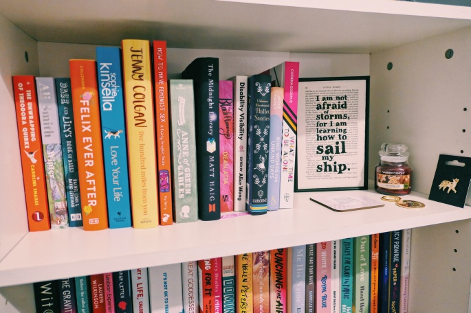 A photo of one of Charlotte's bookcases zoomed into the top shelf, with the second slightly in view. You can see an assortment of books. The top shelf also has a quote saying 'I am not afraid of storms for I am learning how to sail my ship' (from Little Women), a Glittering Star Yankee candle, a fox pin-badge, a key chain and a coaster.